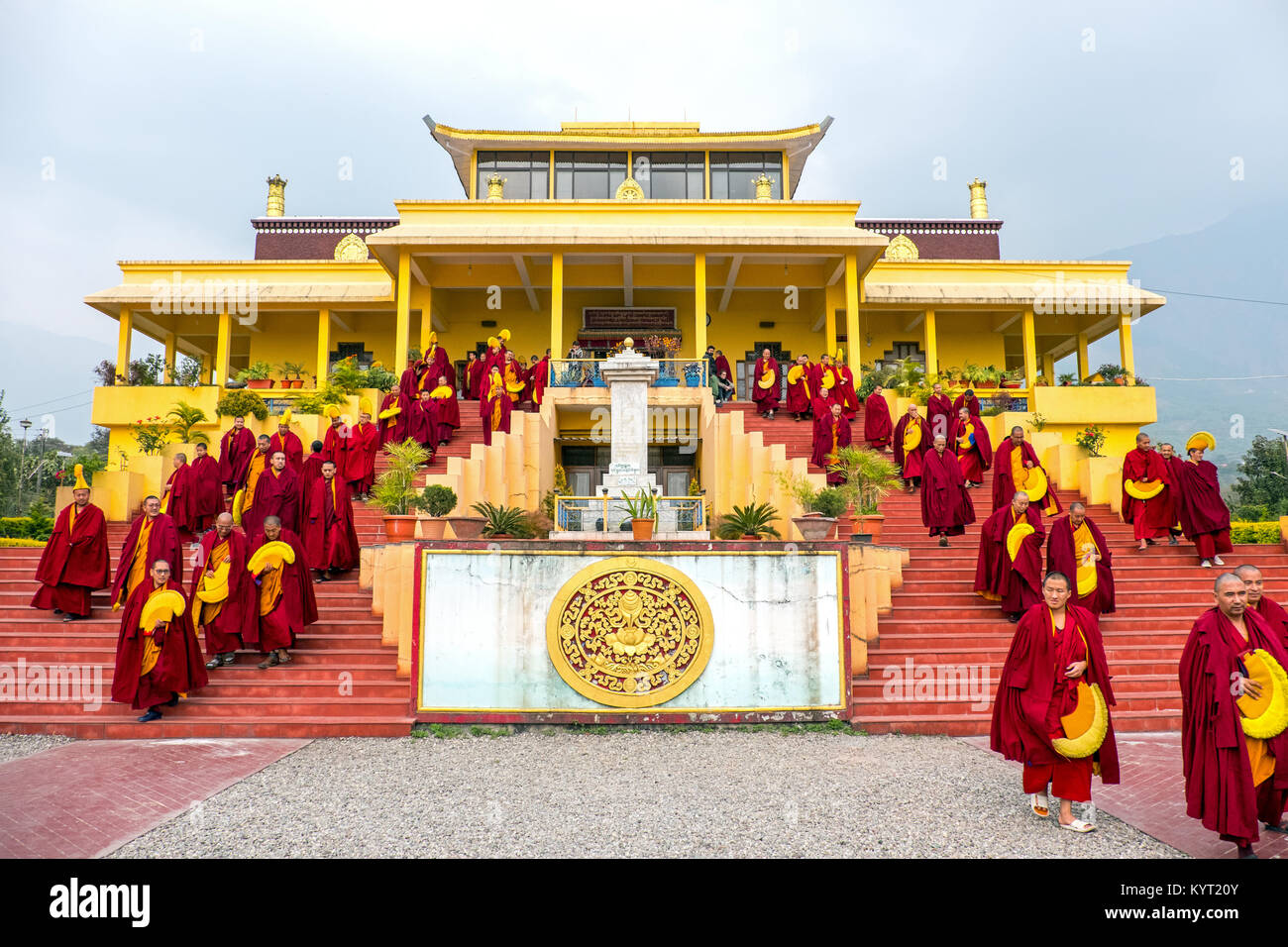 Tibetan monks streaming out of a parayer hall at a Tibetan Buddhist Monastery in Dharamshala, India - Stock Image