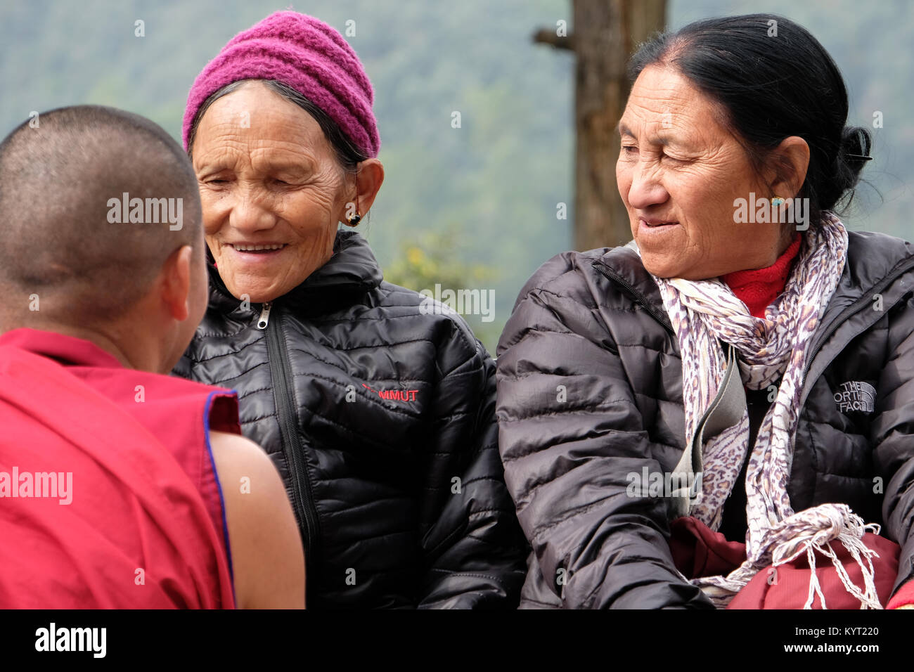 Two Tibetan refugees in Dharamshala, India, talking to a Buddhist monk - Stock Image