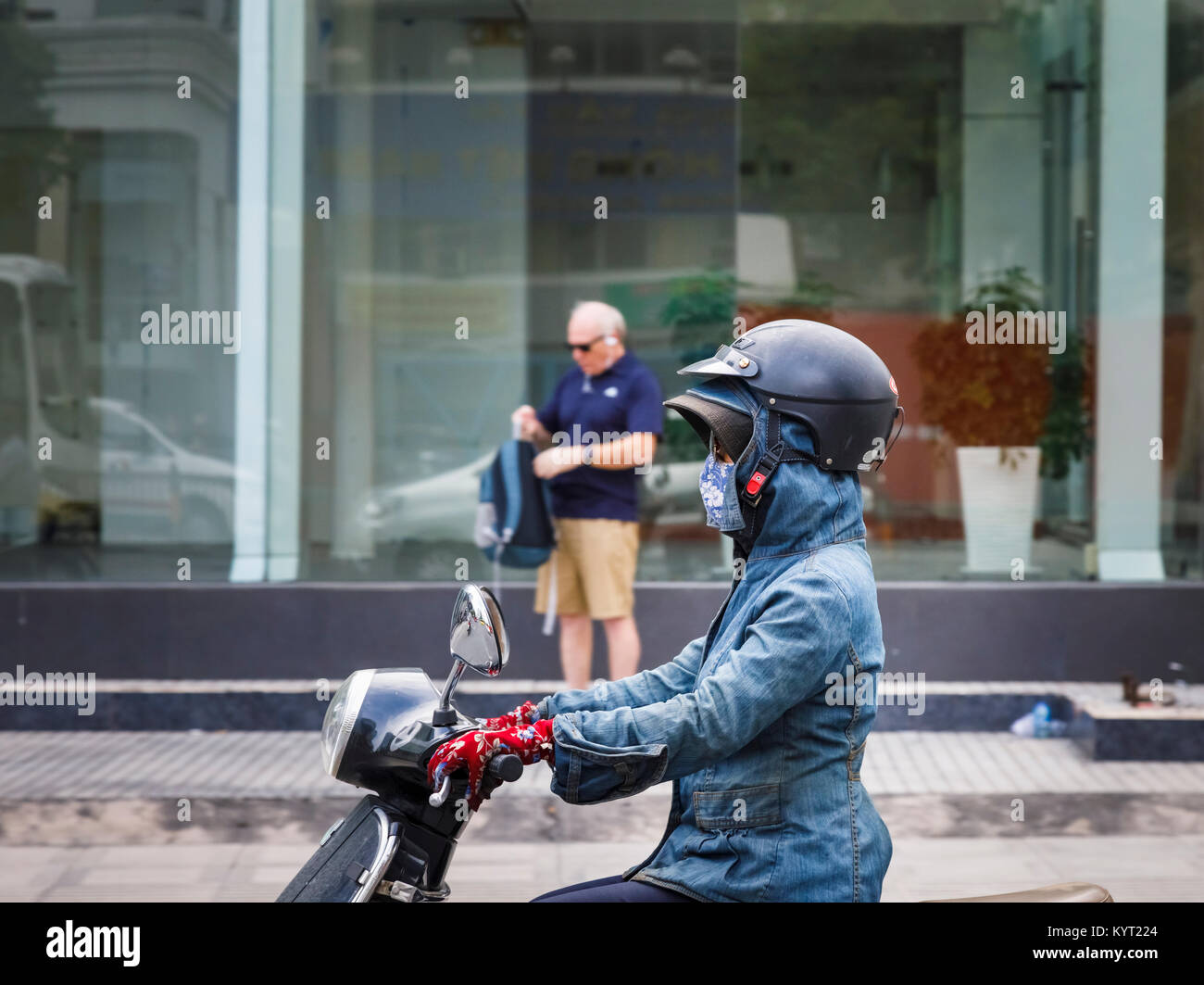 Female motorcyclist wearing an unsafe crash helmet incorrectly over a hat and a hood: street scene in Saigon (Ho Stock Photo