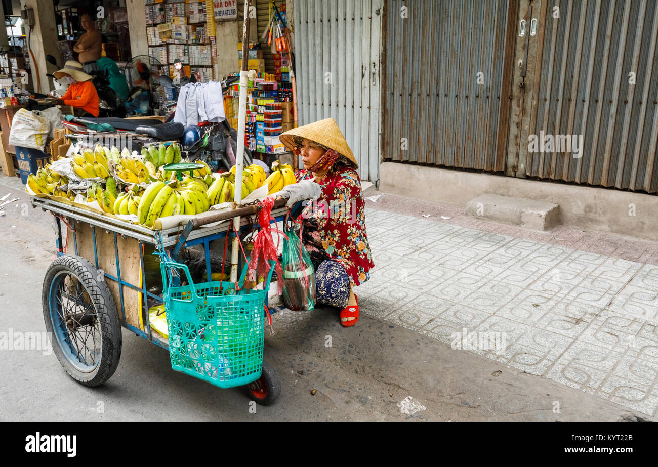 Local woman wearing a coolie hat selling bananas on the roadside from a barrow: street view in suburban Saigon (Ho Stock Photo