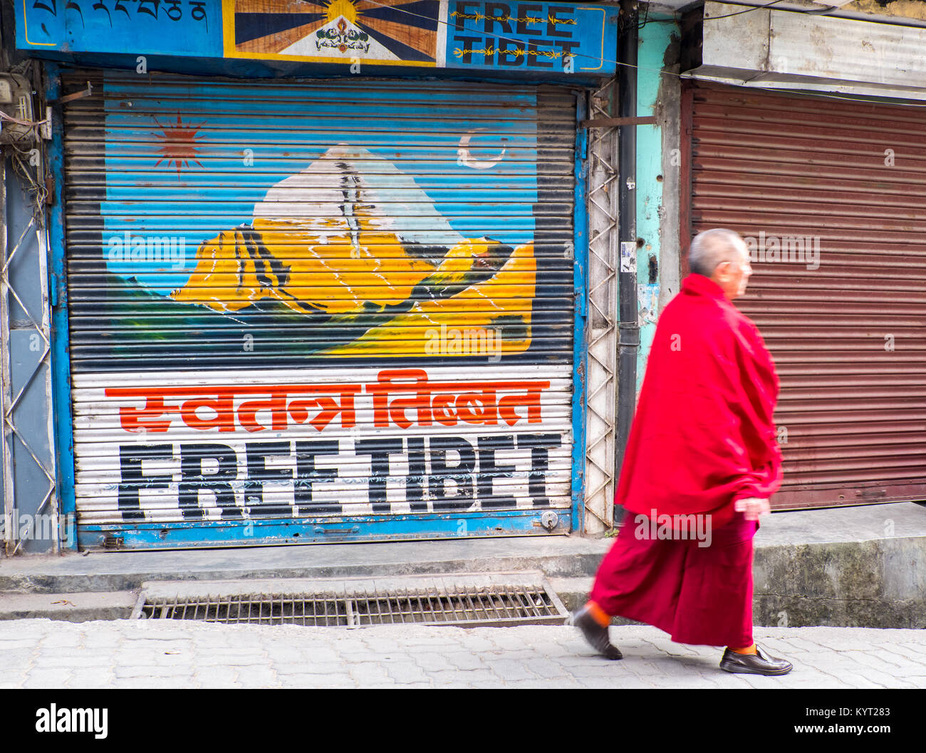 A Tibetan monk walking past a 'Free Tibet' mural in Dharamshala, India, the home of the Tibetan Government - Stock Image
