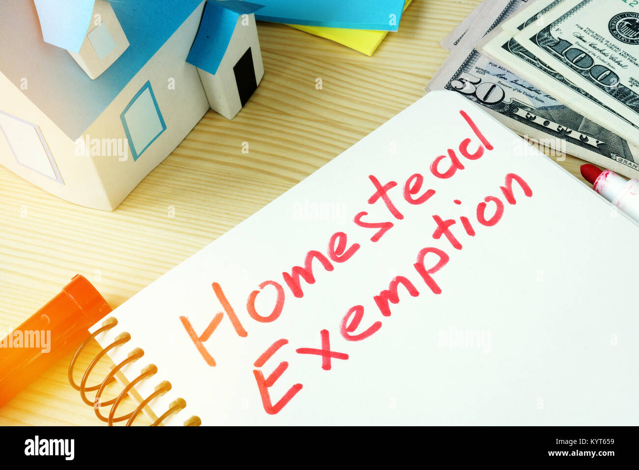 Man writing Homestead Exemption in a note pad. - Stock Image