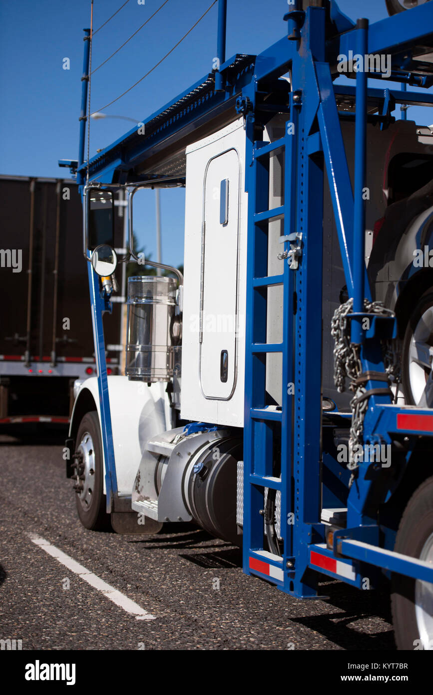 A classic simple powerful bright white big rig semi truck with a two-tier car hauler trailer for the transport of Stock Photo