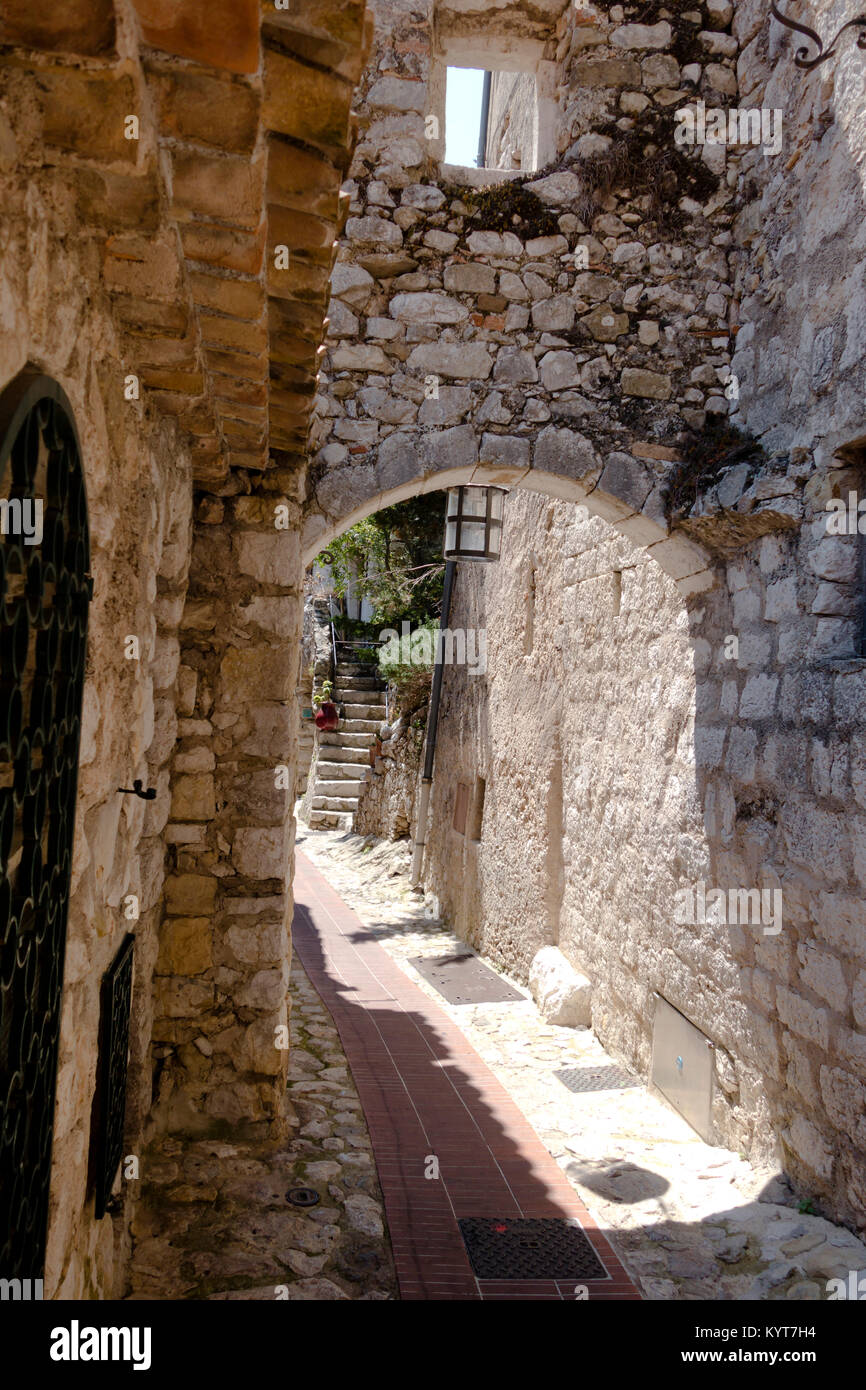 Popular with tourists narrow alley with buildings and staircase of white rocks in old retro part of the village - Stock Image