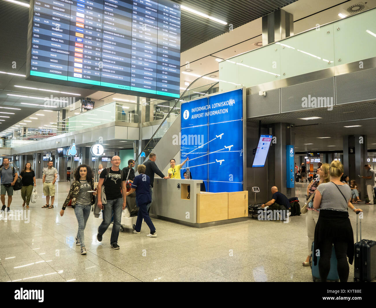 Krakow, Poland - June 6, 2017: Information desk, passengers and a woman showing the direction at the international - Stock Image