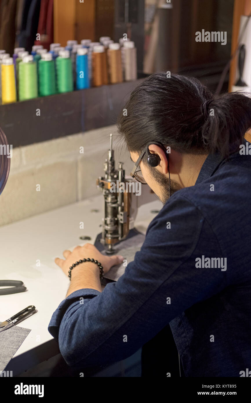 A young man in his twenties sewing on a sewing machine at the Levi's store on West 14th Street in the Meatpacking - Stock Image