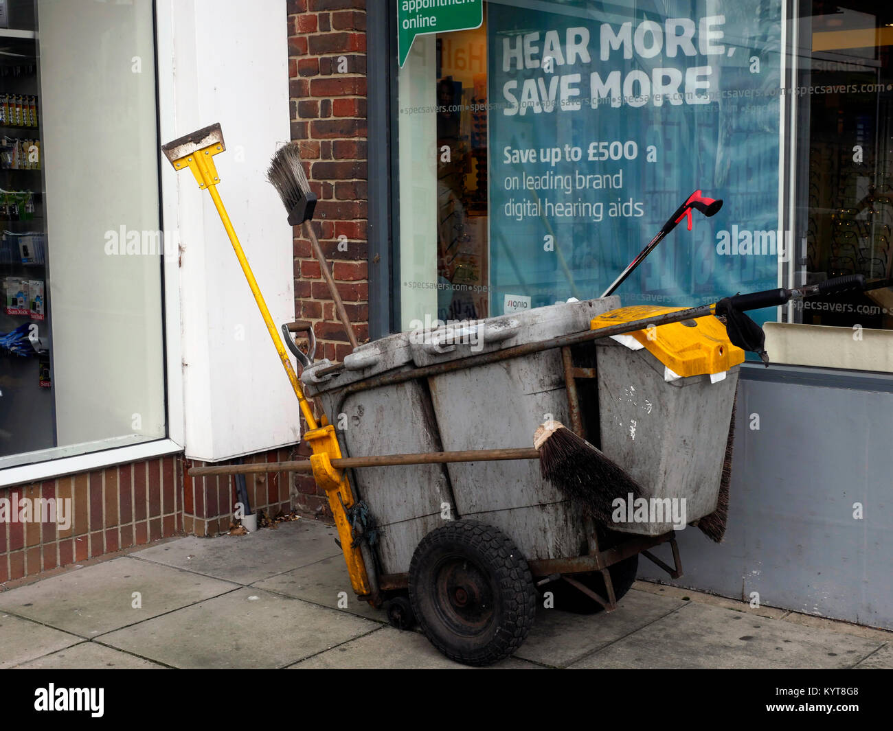 Street sweeper hand dustcart with bins and brushes on High Street, Cosham, Hampshire, England, UK Stock Photo