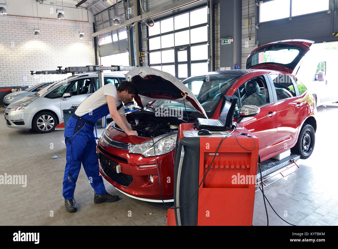 mechanic repairs motor from an automobile with the help of a diagnostic computer - Stock Image
