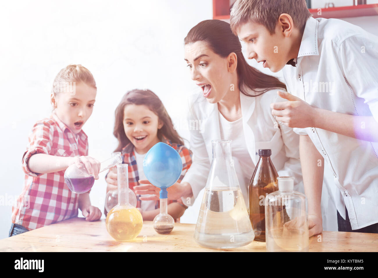 Maybe it was the wrong decision. Frightened little chemists and their teacher worrying about their dubious idea - Stock Image