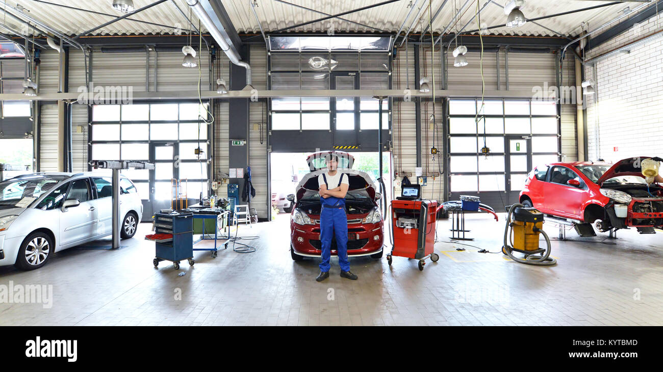 portrait of a successful mechanic in a garage - repair and service of vehicles - Stock Image