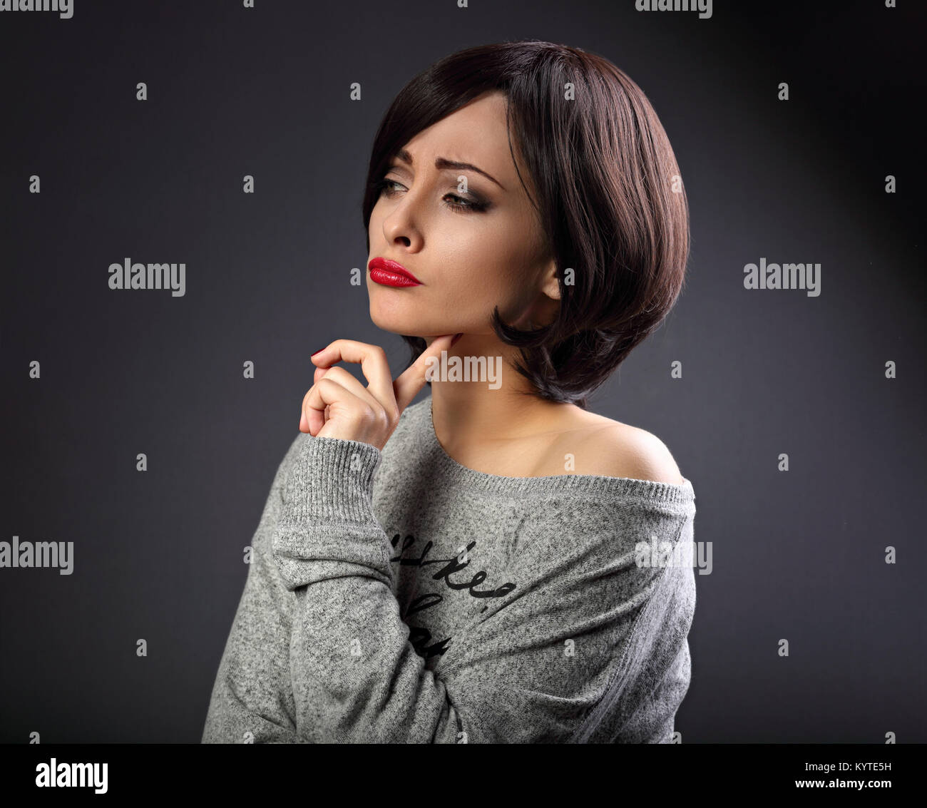 Skeptical unhappy grimacing thinking young woman with short black hair style looking up on empty copy space grey - Stock Image