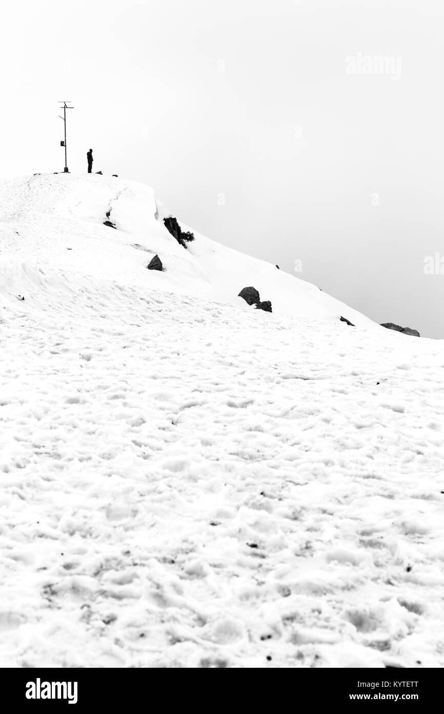 Solo Trekker man stands on top of triund hill top at Mcleod ganj, Dharamsala, Himachal pradesh, India. Beautiful - Stock Image