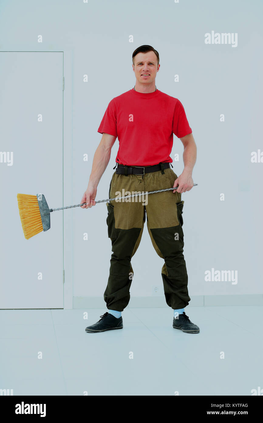 Full length portrait of a cleaner in a uniform with a broom isolated white background. - Stock Image