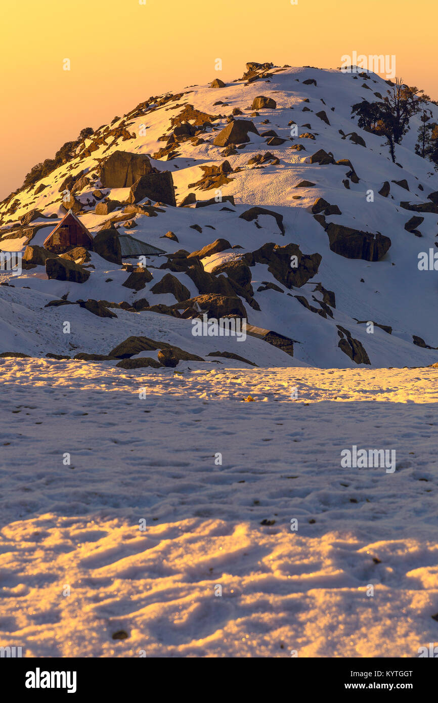 First rays of sun falling on a snow mountain called Triund in Mcleodganj,Dharamshala, Himachal pradesh, India at - Stock Image