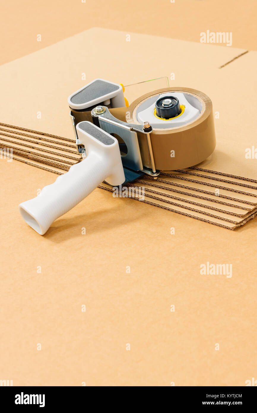 Industrial flat pack cardboard boxes or cartons with a generic tape gun a commercial packaging or despatch concept - Stock Image