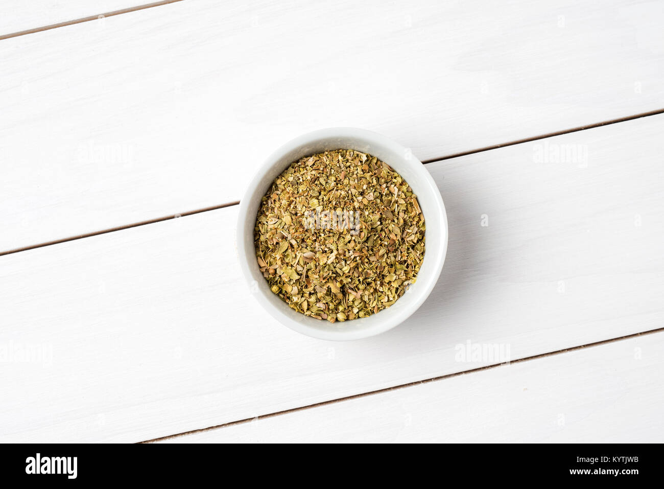 Dried marjoram in white bowl. Close up - Stock Image