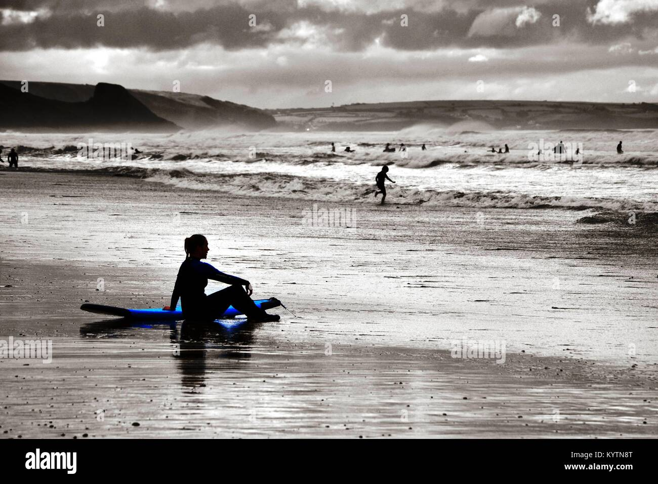 Surfer resting Newgale beach with high sea and surf during summer storm - Stock Image