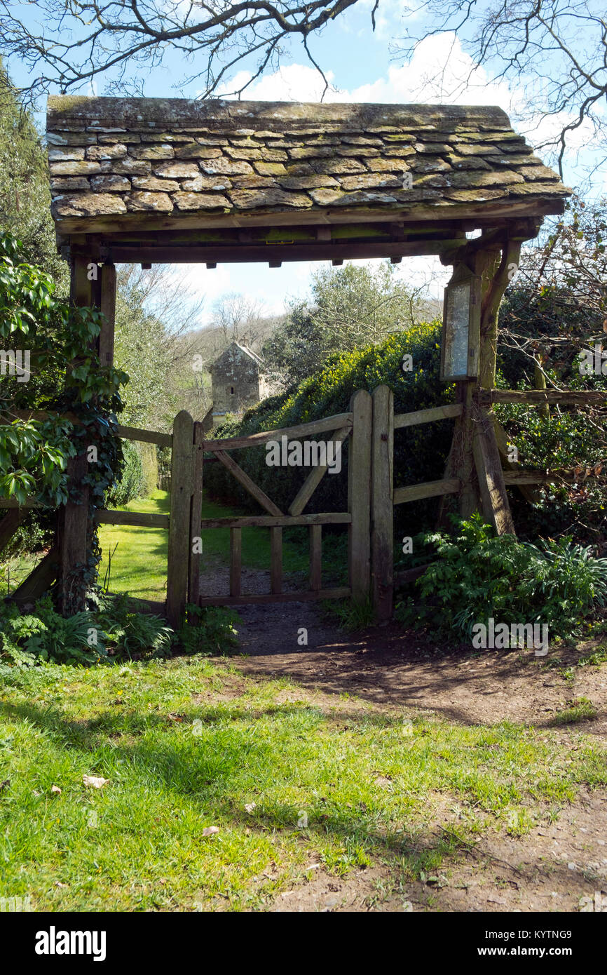 Spring sunshine on the picturesque lychgate to the tiny old Saxon church at Duntisbourne Rouse in the Cotswolds, - Stock Image