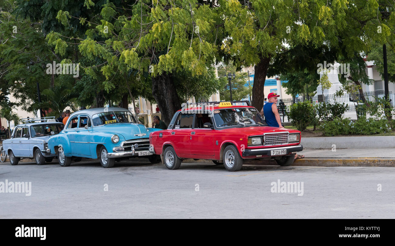 HOLGUIN, CUBA - AUGUST 31, 2017: Taxi drivers parked next to curb on