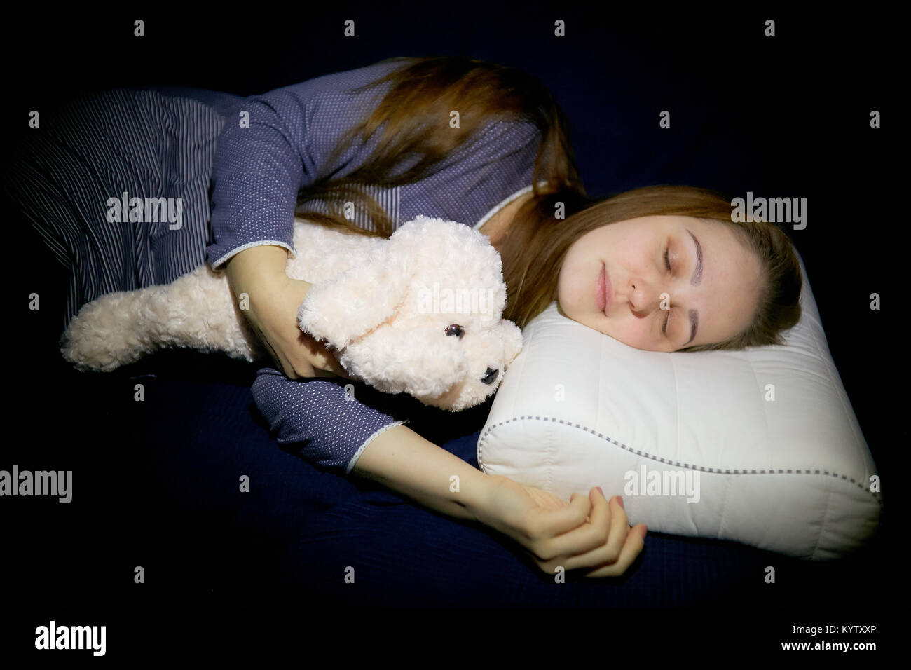 a young woman is sleeping on an orthopedic pillow with a soft indushka in a blue nightgown - Stock Image