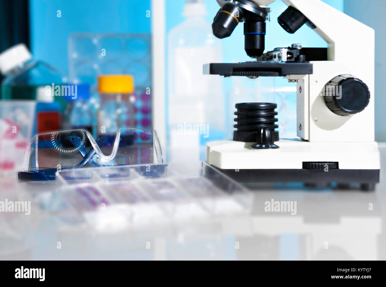 Entry level microscope and plastic safety glasses in scientific lab - Stock Image