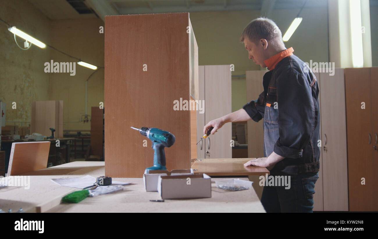 Carpenter working with an electric industrial stapler on the factory, fixing furniture details - Stock Image