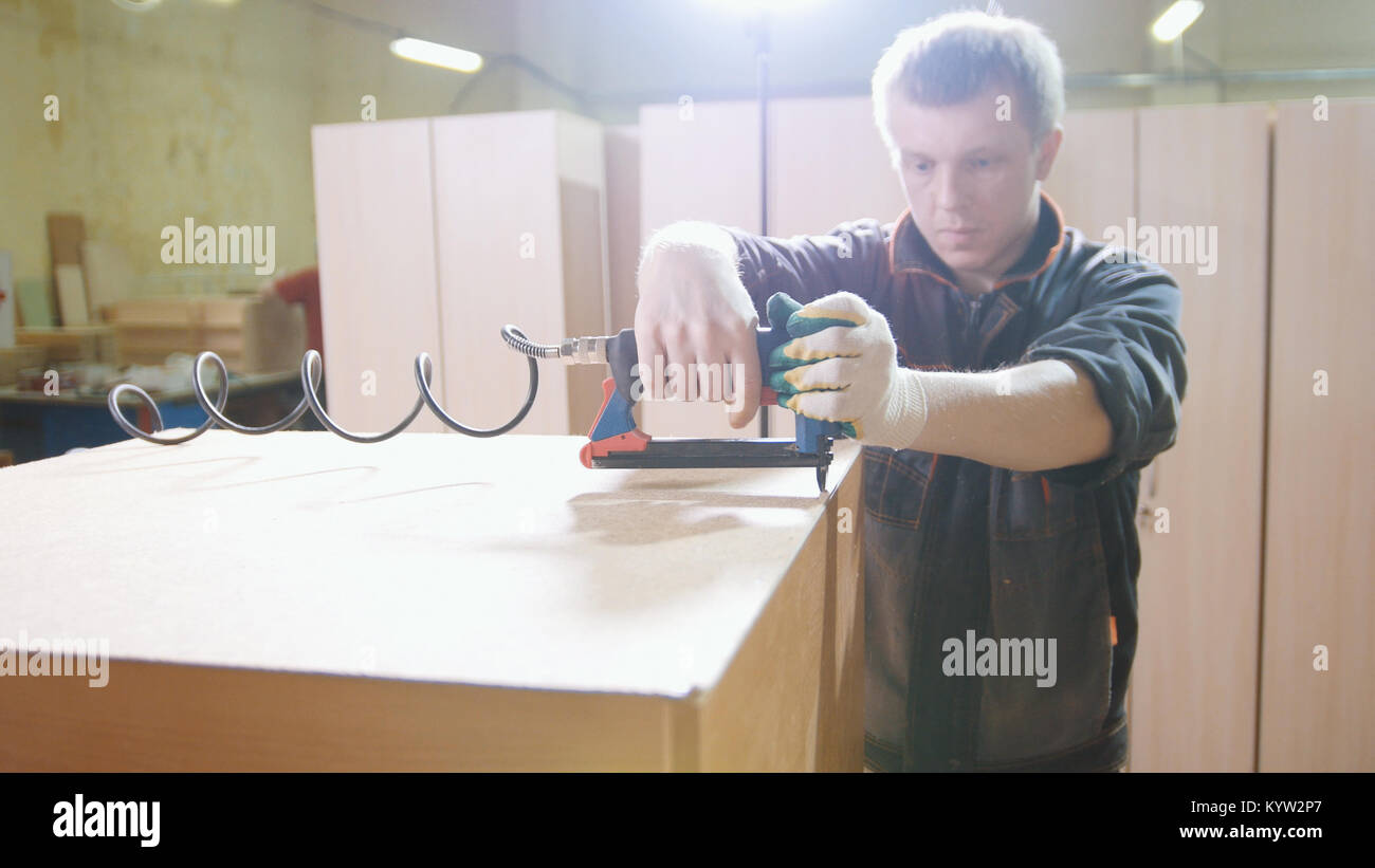 Carpenter working with an electric industrial stapler on the factory, fixing furniture details, close-up - Stock Image