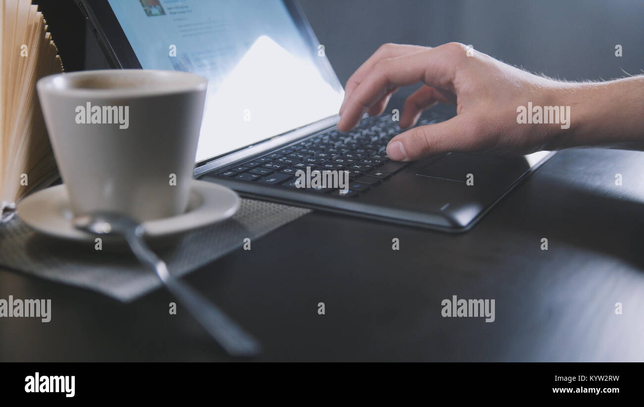 Man drinking coffee and use laptop in cafe - close up Stock Photo