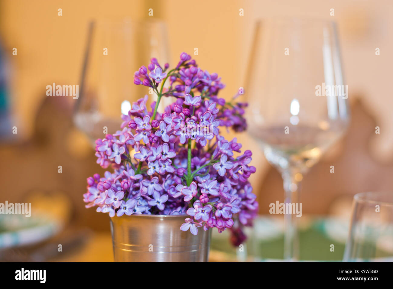 Lilac flowers as spring bouquet in a metal cup on a table setting with wine glasses in the background. Warm shades - Stock Image