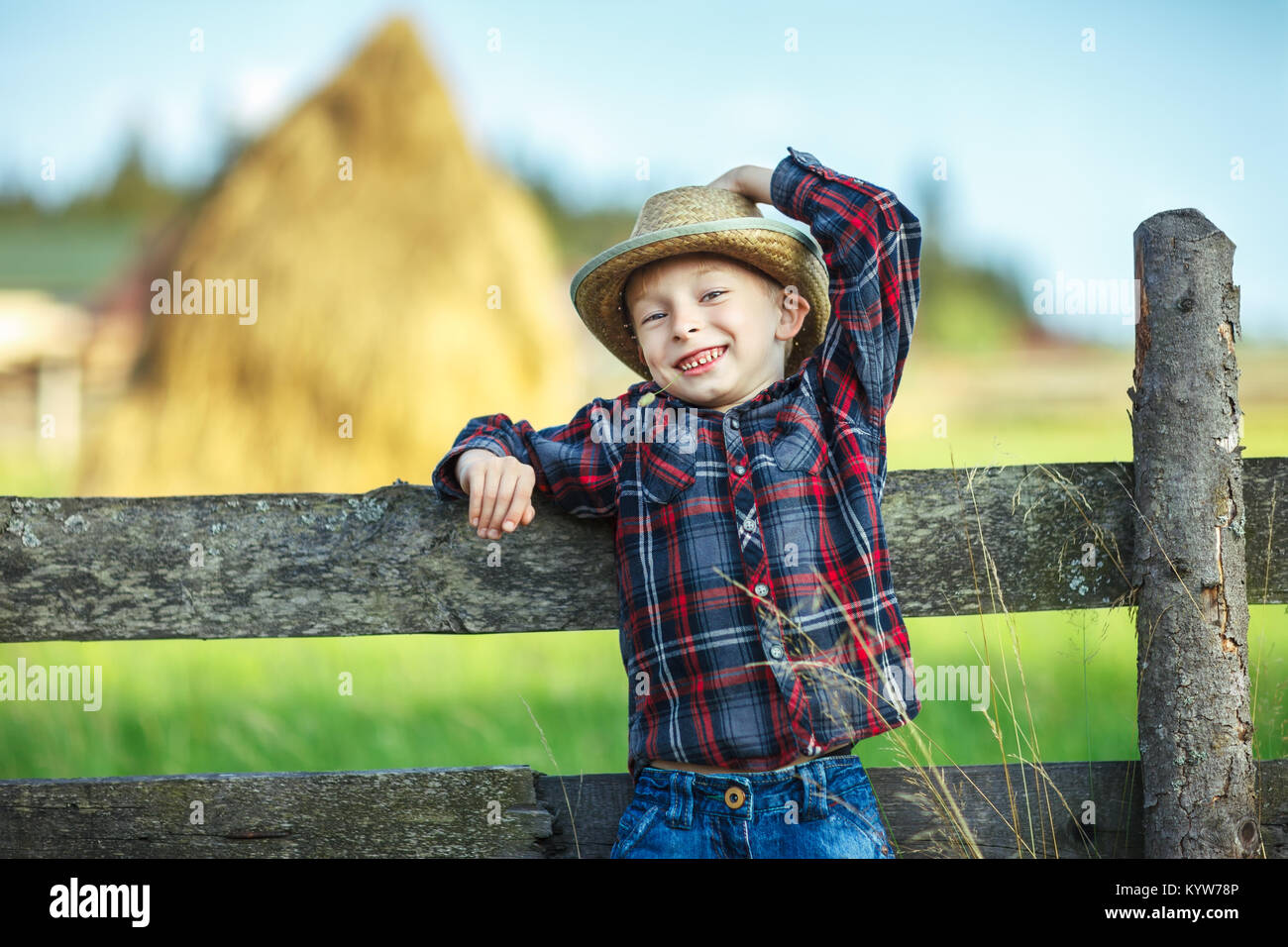 Close up portrait of little boy in hat with straw in mouth leaned on wooden fence. Happy chilhood concept. Vacation - Stock Image