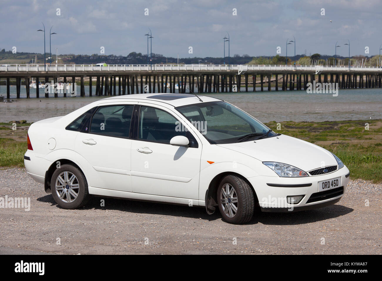 A white 2004 Ford Focus 1.6 Ghia saloon, parked with Hayling Island bridge in the background - Stock Image
