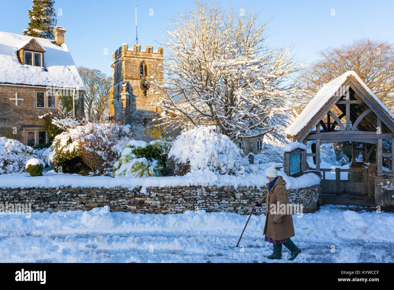 Walking home in the late afternoon on a snowy day past the church of St Andrew in the Cotswold village of Miserden, - Stock Image