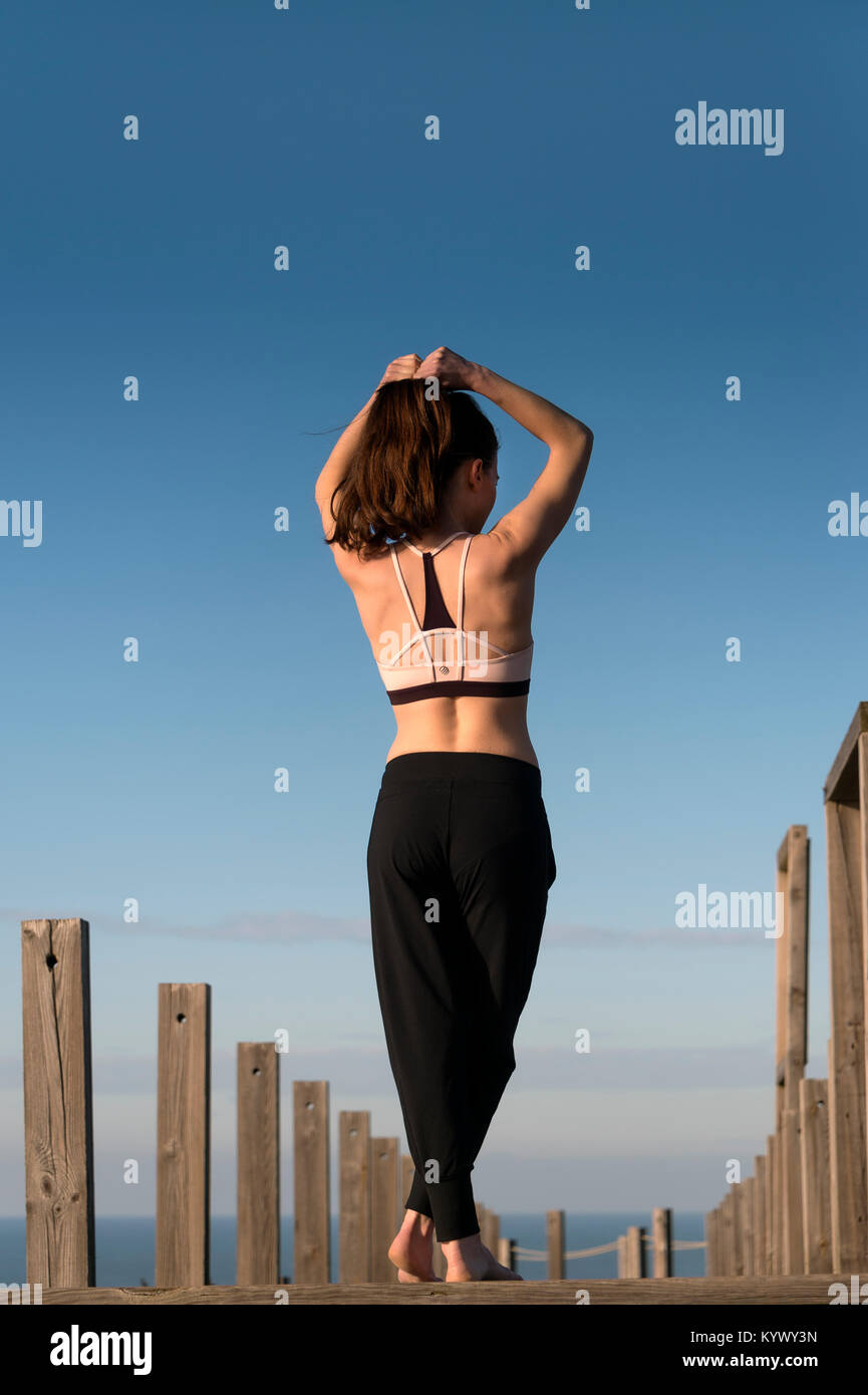 woman tying her hair back before fitness training outside by the sea. - Stock Image