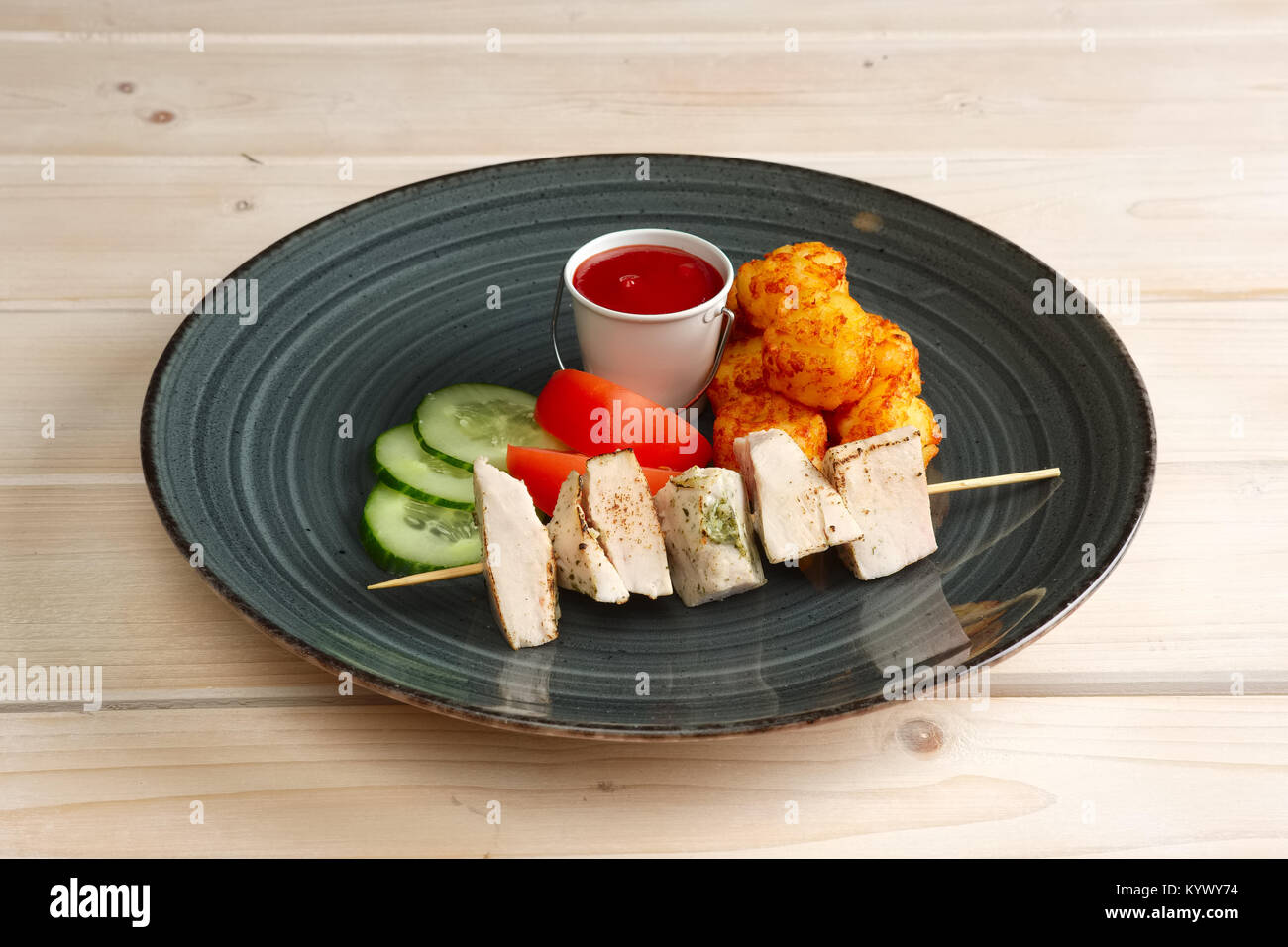 Pieces of chicken fillet on skewer with fried potato balls and vegetables - Stock Image