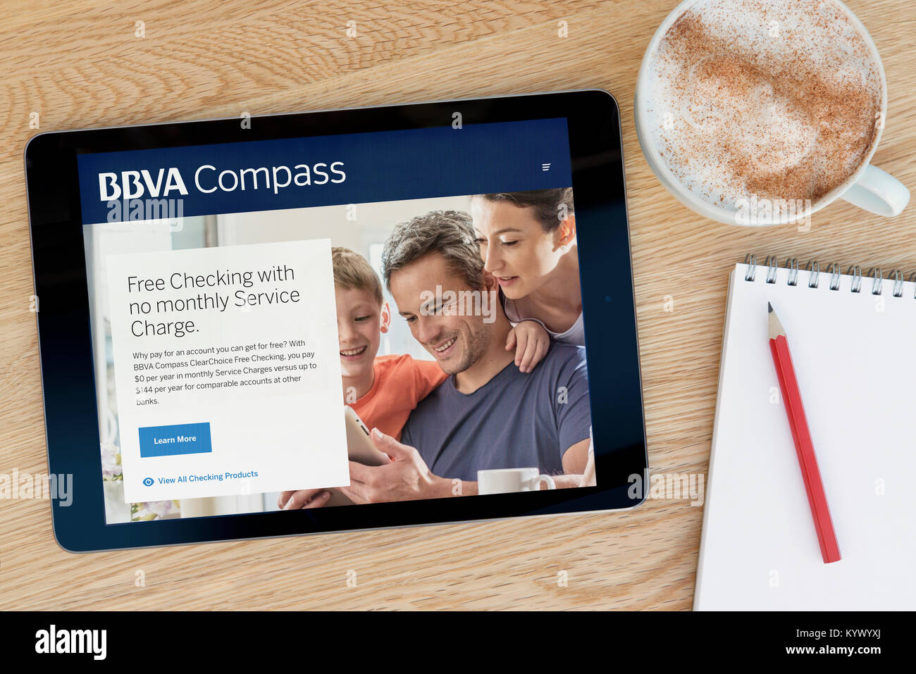 The BBVA Compass website on an iPad tablet, on a wooden table beside a notepad, pencil and cup of coffee (Editorial - Stock Image
