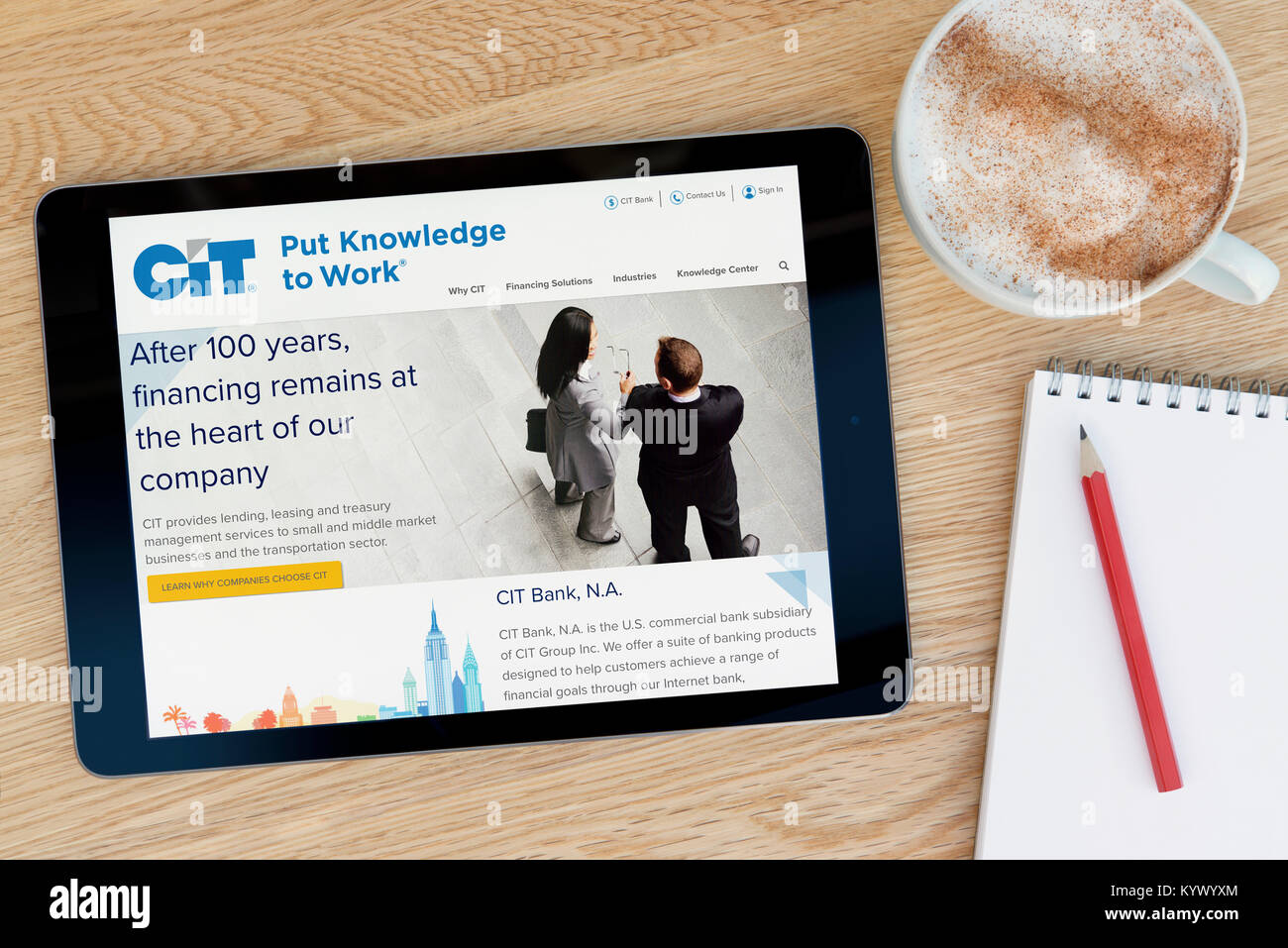 The CIT Group website on an iPad tablet, on a wooden table beside a notepad, pencil and cup of coffee (Editorial - Stock Image
