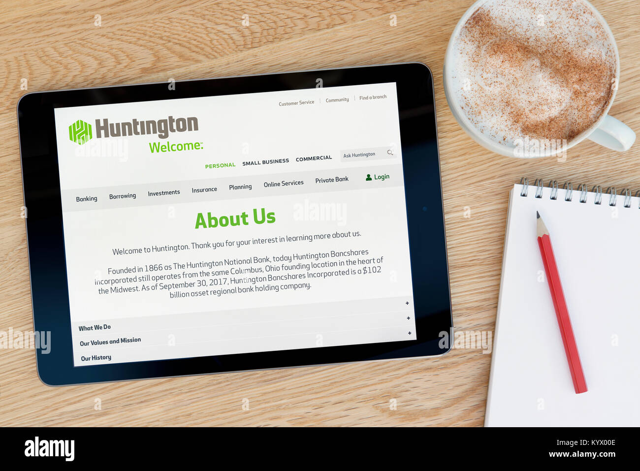 The Huntington Bancshares website on an iPad tablet, on a wooden table beside a notepad, pencil and cup of coffee - Stock Image
