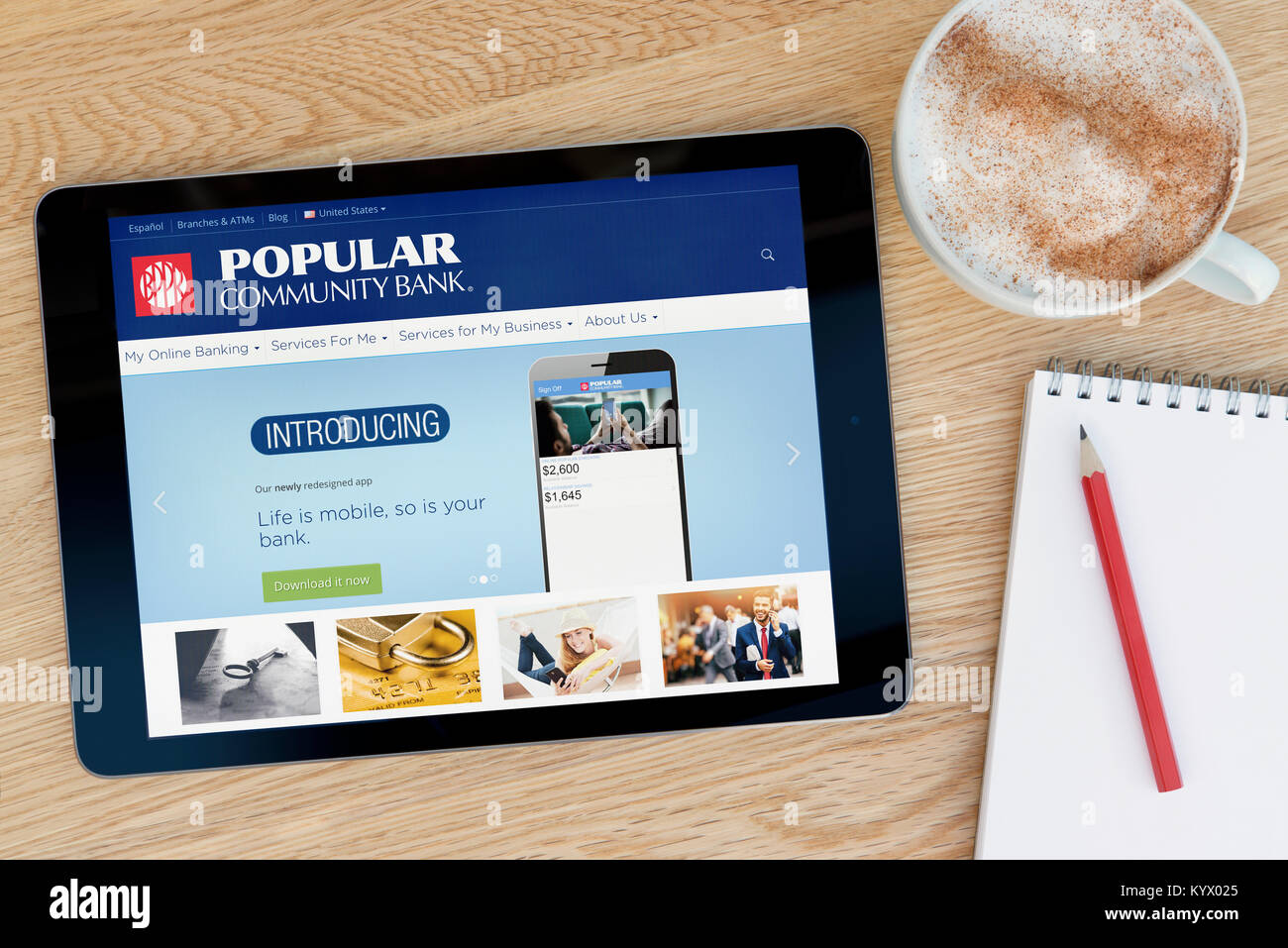 The Popular Community Bank website on an iPad tablet, on a wooden table beside a notepad, pencil and cup of coffee - Stock Image