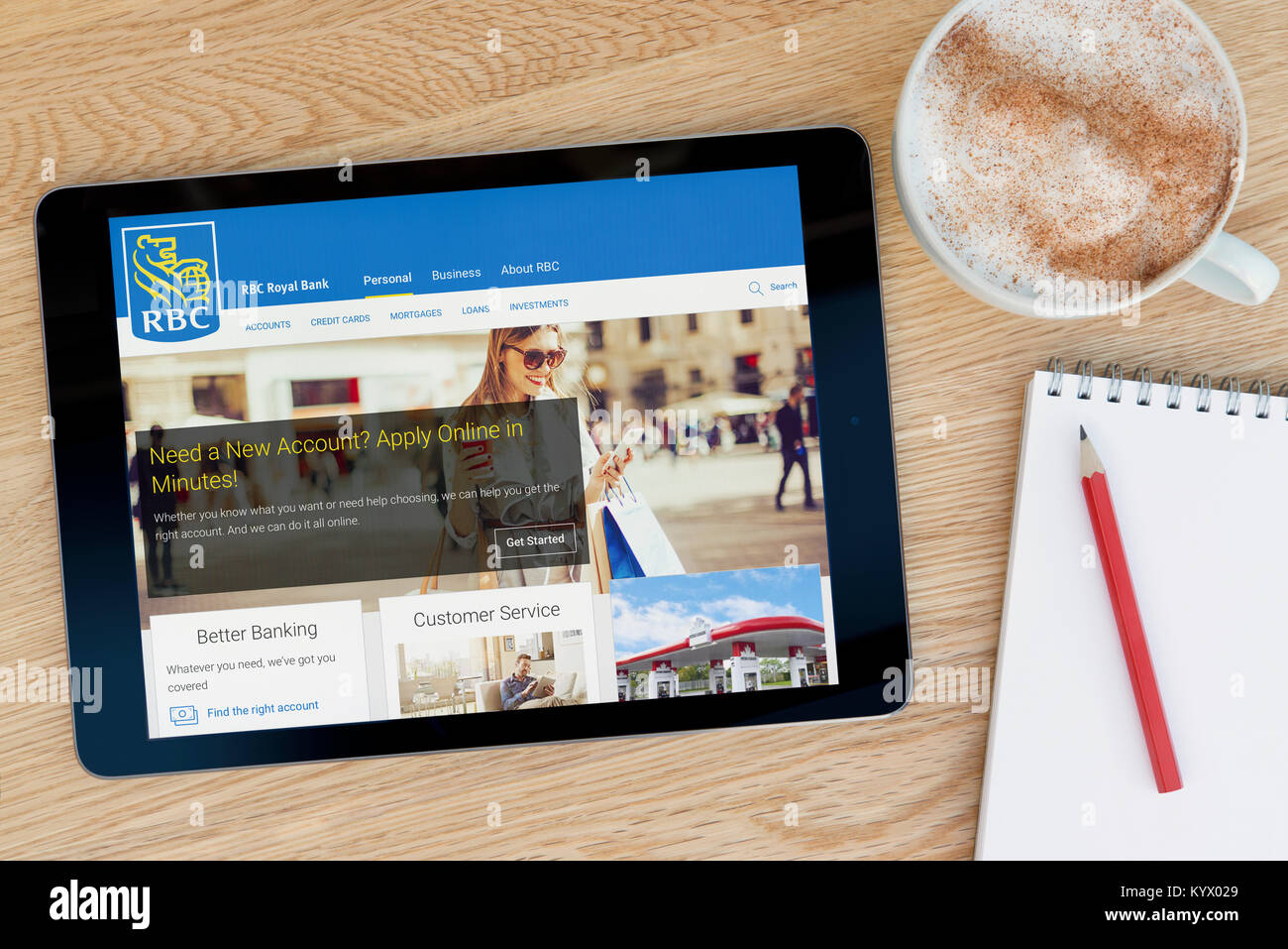 The Royal Bank of Canada website on an iPad tablet, on a wooden table beside a notepad, pencil and cup of coffee - Stock Image