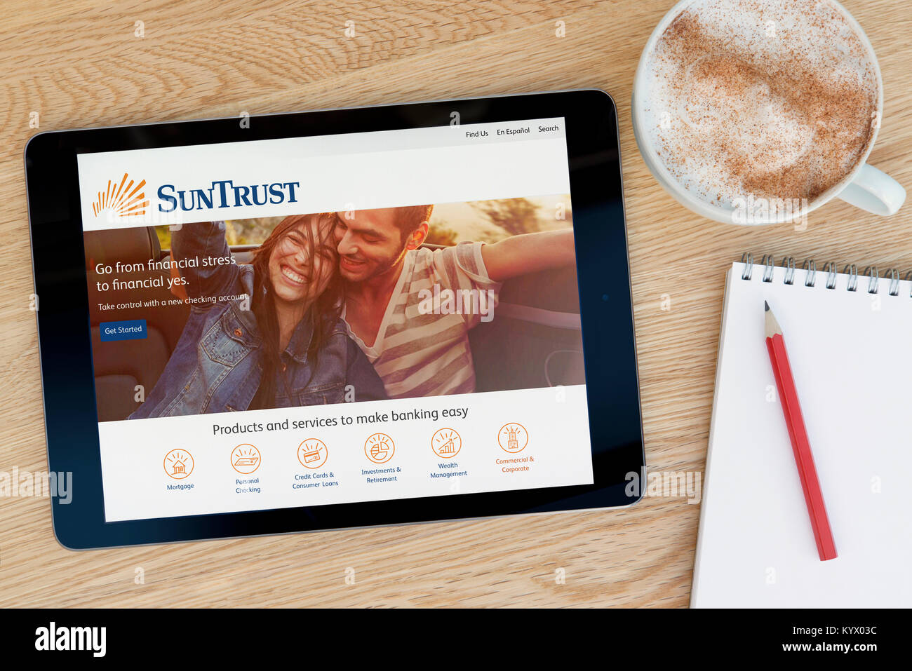 The SunTrust Banks website on an iPad tablet, on a wooden table beside a notepad, pencil and cup of coffee (Editorial - Stock Image