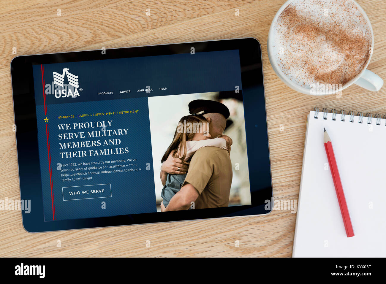 The United Services Automobile Association (USAA) website on an iPad tablet, on a wooden table and notepad, pencil - Stock Image