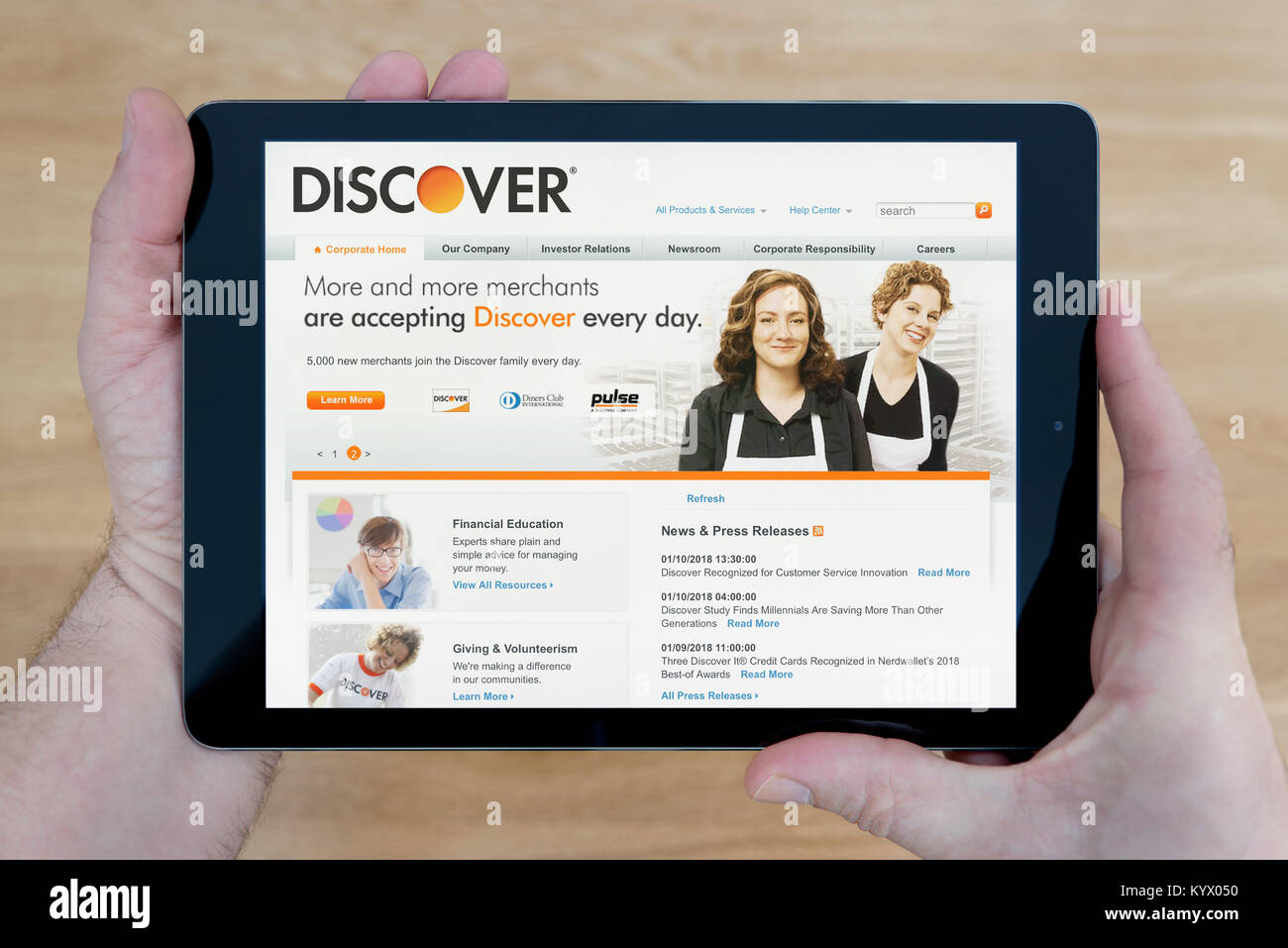 A man looks at the Discover Bank website on his iPad tablet device, with a wooden table top background (Editorial - Stock Image