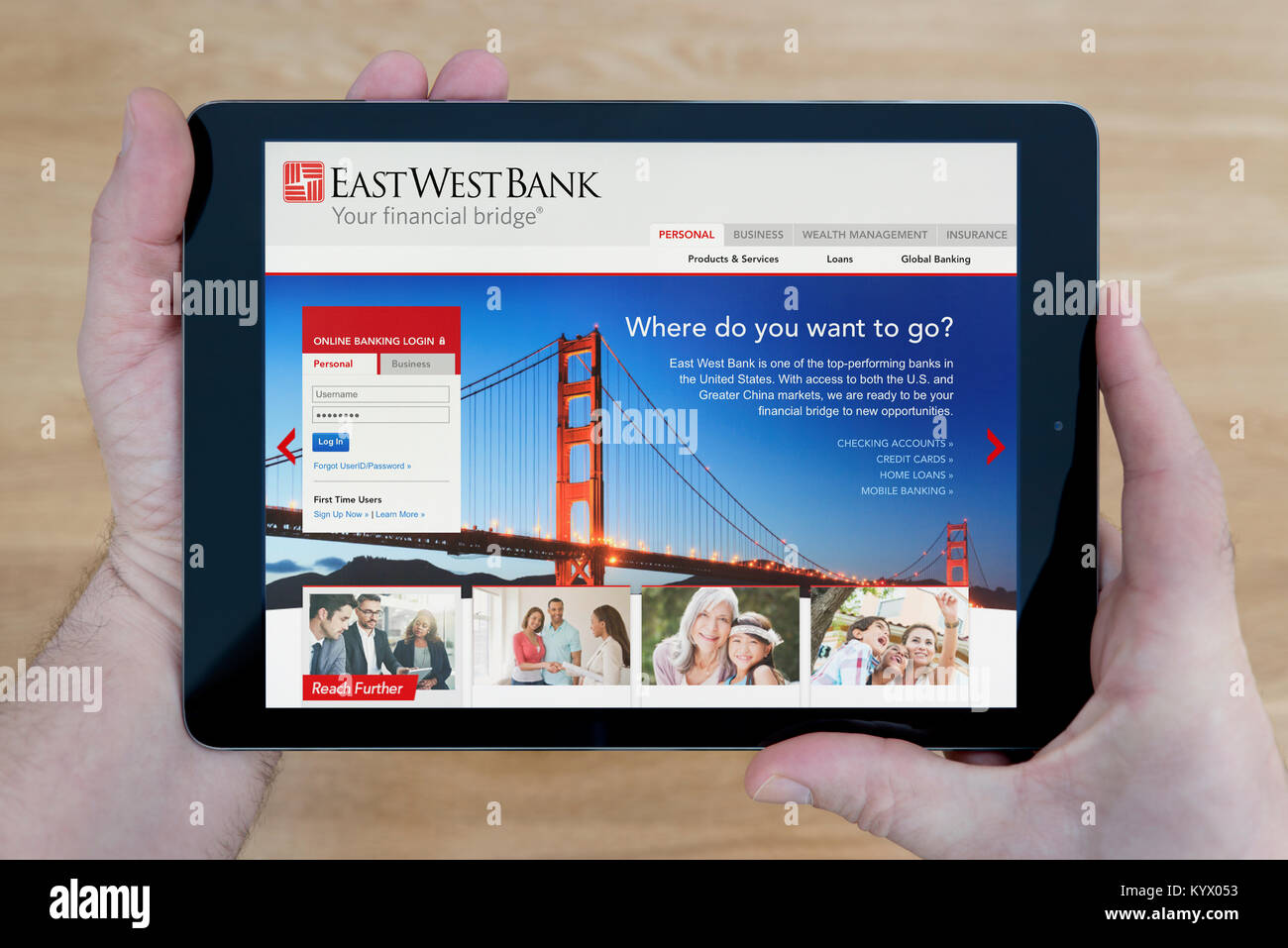 A man looks at the east west bank website on his ipad tablet device a man looks at the east west bank website on his ipad tablet device with a wooden table top background editorial use only voltagebd Gallery