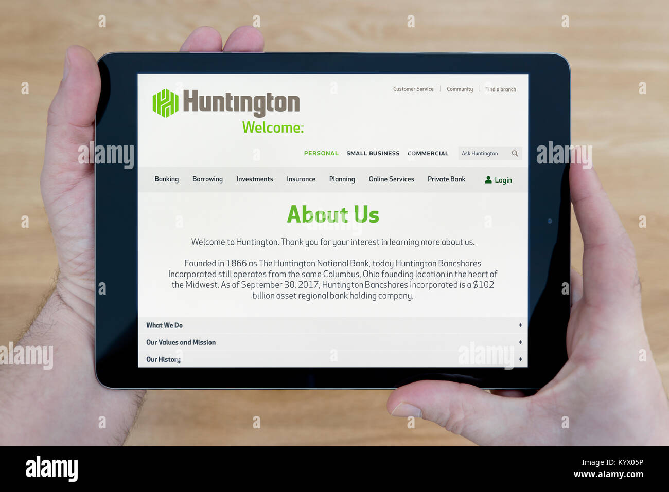 A man looks at the huntington.com website on his iPad tablet device, with a wooden table top background (Editorial - Stock Image