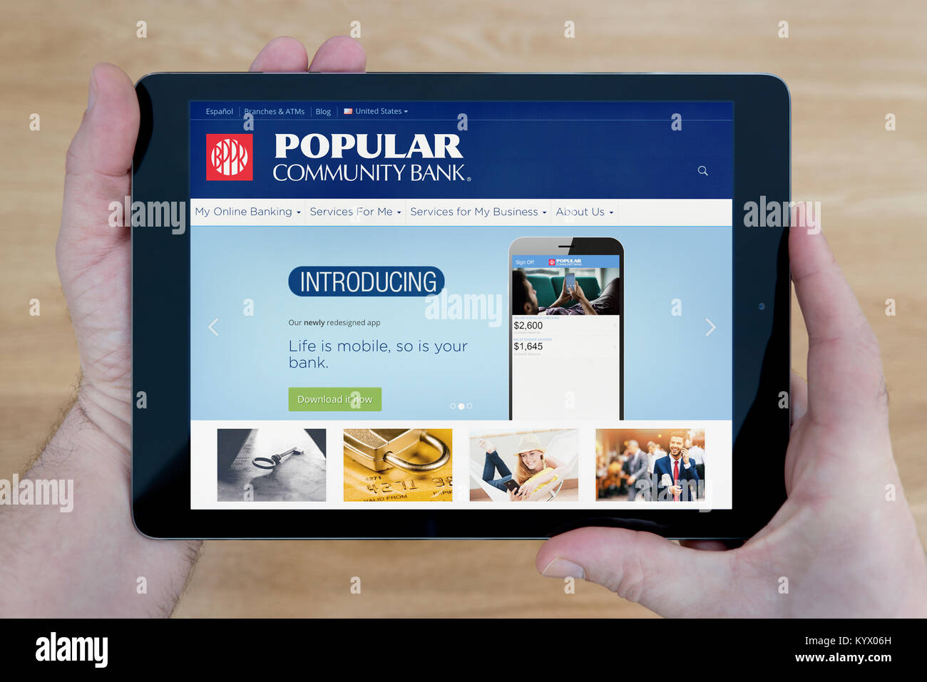 A man looks at the Popular Community Bank website on his iPad tablet device, with a wooden table top background - Stock Image