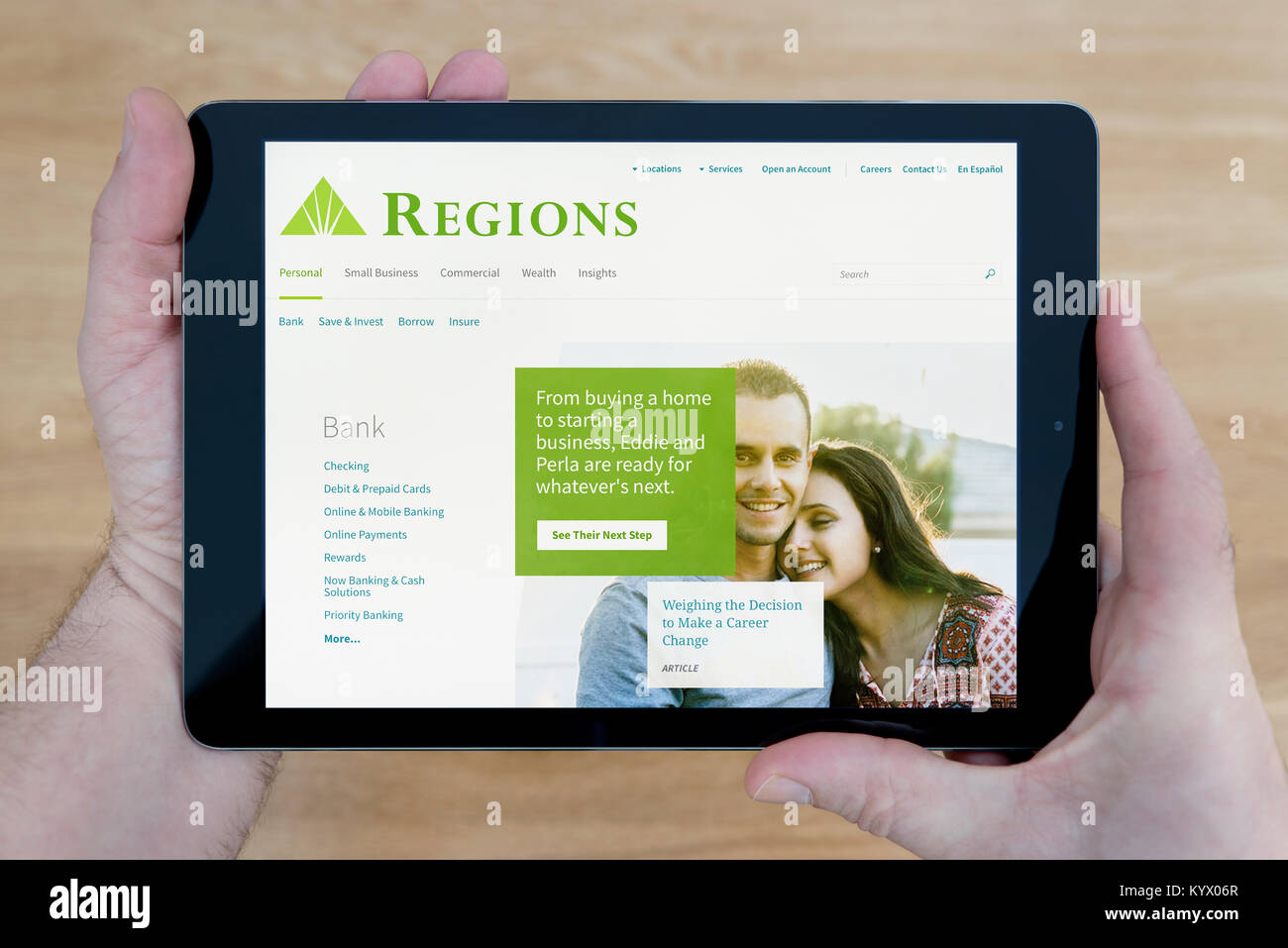A man looks at the Regions Financial Corporation website on his iPad tablet device, with a wooden table top background - Stock Image