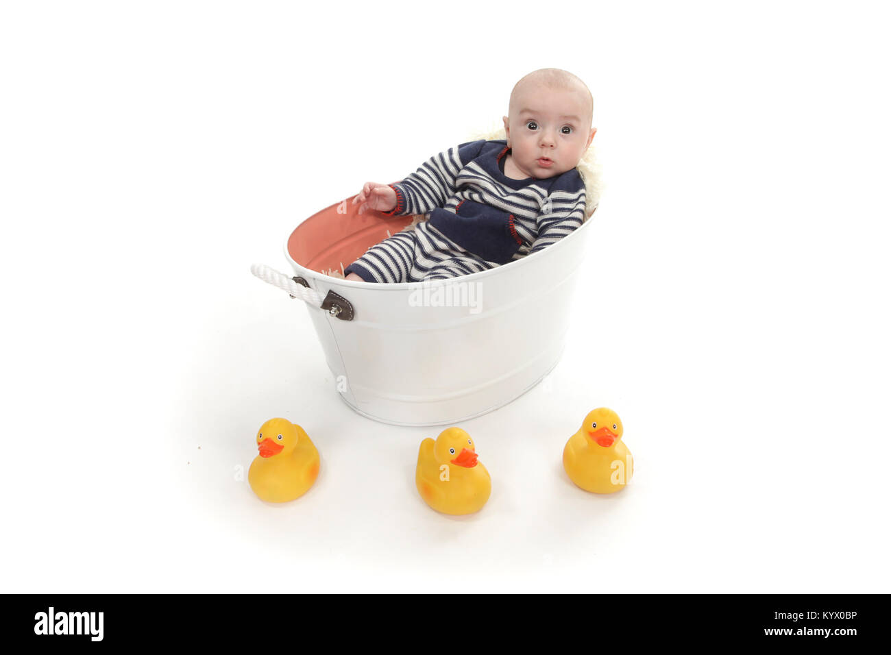12 week old baby boy exploring in tin bath tub with rubber ducks - Stock Image