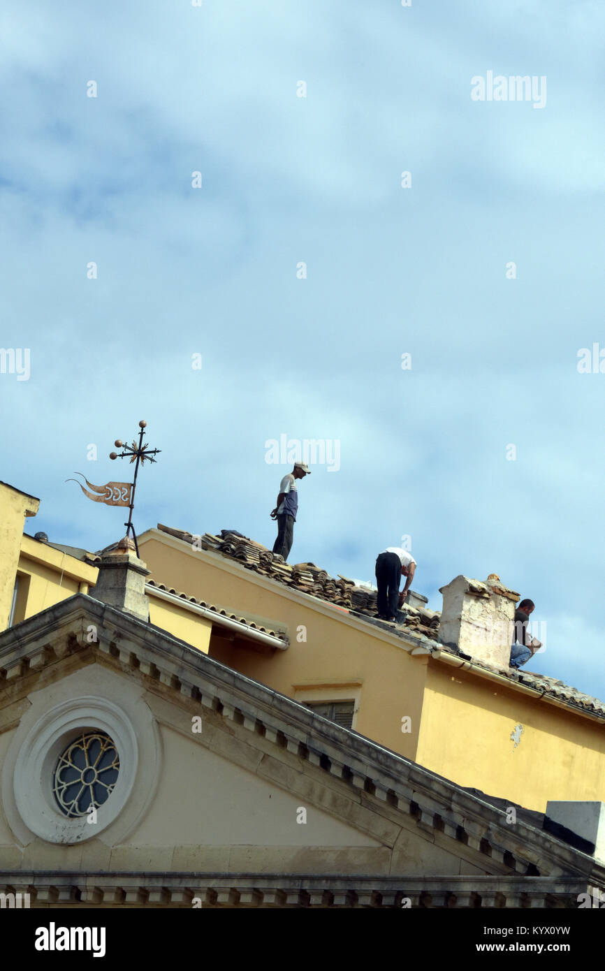 A bad example or practice of poor health and safety on a building site rooftop in the Greek town of kerkira on Corfu. - Stock Image