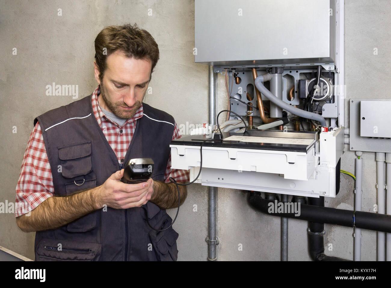 plumber repairing a condensing boiler - Stock Image