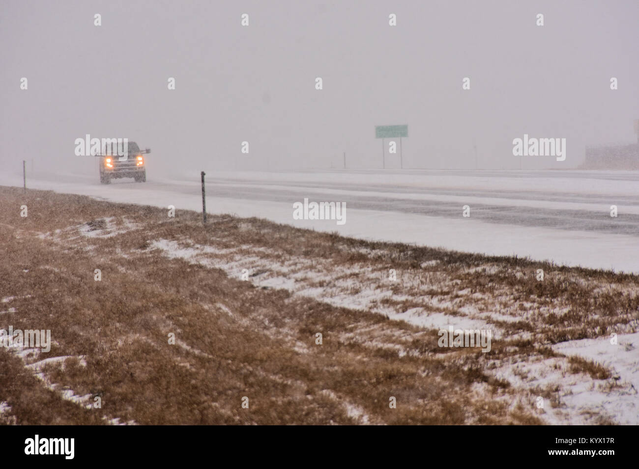 Vehicles traveling on slippery icy road in snow storm. - Stock Image